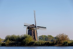 Summer landscape view with beautiful traditional Dutch windmill under blue clear sky in sunny day, Trees along countryside road on the Vecht river, Nigtevecht, Province of Utrecht, Netherlands.