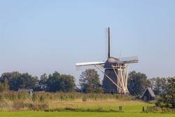 Summer landscape view with beautiful traditional Dutch windmill under blue clear sky in sunny day, Countryside road on the Vecht river, Loenderveense Molen, Loenen aan de Vecht, Utrecht, Netherlands.