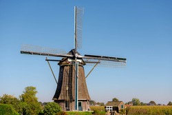 Summer landscape view with beautiful traditional windmill under blue sky, Dutch agriculture in countryside with corn or maize field along the Vecht river, Nigtevecht, Province of Utrecht, Netherlands.