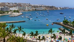 Summer landscape with a beach with people bathing, hotels and boats anchored in the sea. Gran Canaria. Arguineguin.