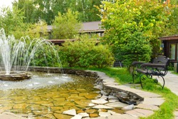 Summer landscape with a beautiful carved beautiful bench at the fountain. A cozy quiet place to relax in nature. Stone fountain in a city park. A metal bench by the water in the garden.