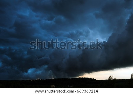 Summer landscape with black storm clouds in the sunset sky