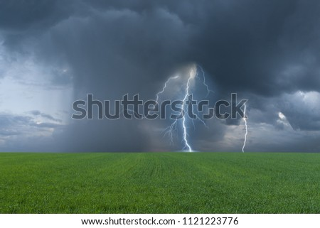 Summer landscape with green field and thunderstorm, lightning and majestic clouds