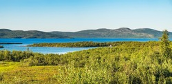 Summer landscape with green medow and lake, forest and village on horizon near Sangis in Kalix Municipality, Norrbotten, Sweden. Swedish landscape in summertime.