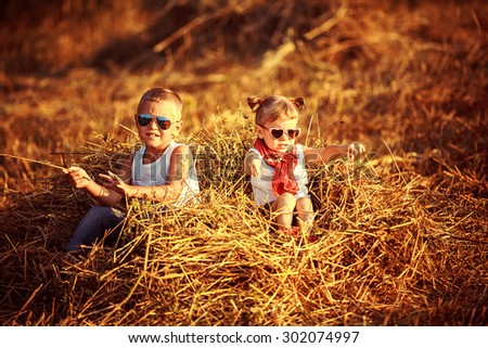Summer landscape with hay cocks, couple children, brother and sister sitting on large pile of hay