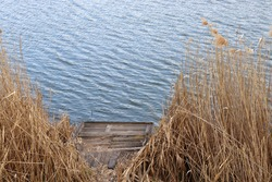 Summer landscape with old wooden fishing pier on the river among the dry reeds. Windy weather. Waves on the water. Reeds on the bank of lake