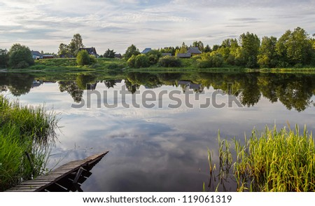Summer landscape with the lake and clouds. The rural river in Russia
