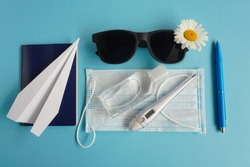Summer layout with daisies and sunglasses, airplane-origami, sanitizer, passport and medical mask. Concept of travel and recreation. Flights to sea, rest during coronavirus. Flatlay on blue