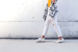 Summer lifestyle fashion of young stylish hipster woman walking on street.
