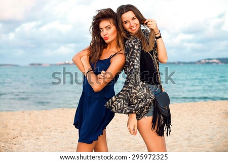 Summer lifestyle fashion portrait of young woman in stylish outfit holding hat and walking near ocean, positive mood,vintage toned colors.Party girls,friends having fun,girls night out,beach party