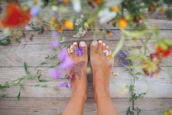 Summer lifestyle portrait of a attractive girl's feet with buds of wildflowers between toes. Staying on wooden terrace surrounded by flowers. Enjoying life, nature. Feet in focus, flowers in blur.