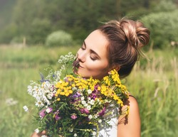 Summer lifestyle portrait  of beautiful young woman smiling and holding bouquet of wild flowers. Standing in the field of grass. Enjoying sun. Happiness and love concept. Сlosed eyes