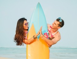 Summer lifestyle portrait of happy smiling couple holding hands. Hiding behind the surfboard. Wearing stylish sunglasses. On honeymoon. Interracial couple, Asian woman, Caucasian man. Close up