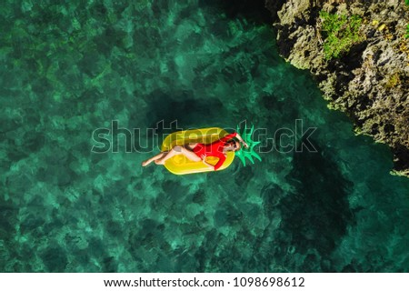 Summer lifestyle portrait of pretty girl swimming on the back on the inflatable pineapple in the ocean, wearing stylish red bikini and sunglasses. Relaxing and enjoying life. Bright colors. Top view