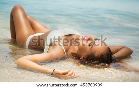Summer lifestyle portrait of pretty young girl with tanned sexy body. Enjoying life, smiling and lying in the clear sea water on the beach of the tropical island . Wearing white bikini  #453700909