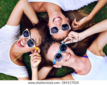 Summer lifestyle portrait of three hipster woman laying on the grass enjoy nice day, wearing white simple tops and bright sunglasses. Best friends girls having fun, joy, playful mood.