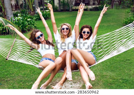 Summer lifestyle portrait of tree girls going crazy, screaming, laughing having fun together, jumping at hammock.  wearing white tops and sunglasses, ready for party,  joy, fun.