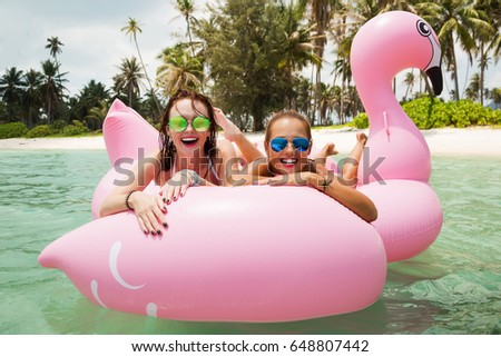 Summer lifestyle portrait of two pretty cheerful girls friends swimming on air mattress in the ocean, wearing bikini and mirrored sunglasses. Smiling and having fun. Positive emotions, bright colors