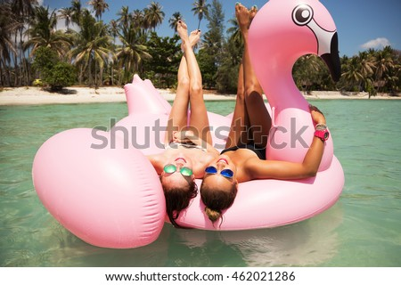 Summer lifestyle portrait of two pretty girls friends having fun on air mattress in the ocean. Wearing bikini and mirrored sunglasses. Smiling and doing yoga. Positive emotions, bright colors