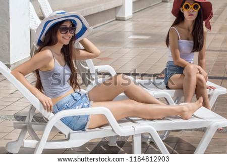 Summer lifestyle young Woman relax near swimming pool sunbath at the beach resort in the hotel.  . Enjoying life  Wearing stylish sunglasses, jeans. Sunbathing. #1184812903