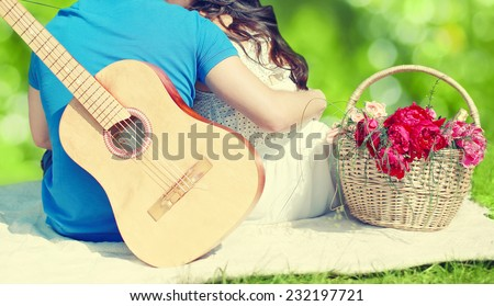 Summer, love, vacation and people concept - lovely young couple in love resting together on the grass near basket with bouquet flowers, man with acoustic guitar hugs his beloved woman outdoors