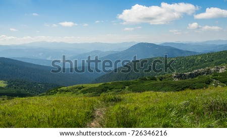Summer low mountains, green grass, and blue sky landscape #726346216