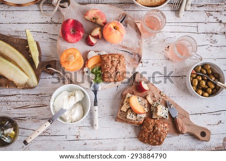 Summer lunch served on a white wooden picnic table with fruits, various cheese, olives and fruits juice  from above. Rustic mediterranean atmosphere outdoors.