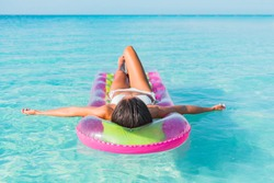 Summer luxury vacation relaxation bikini woman sunbathing lying down on air mattress floating on blue turquoise water paradise beach relaxing sunbathing in Caribbean.