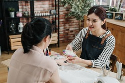 Summer manicure and nail color samples. Master woman manicurist helping customer chooses color of nail polish from palette with lady finger in nail beauty salon. smiling beautician listen client talk