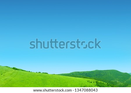 Summer meadow in the mountains, tourism. Beautiful landscape. Fresh green rural meadows on a sunny day with blue sky. Scenery #1347088043
