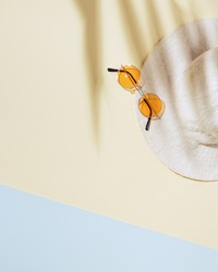 Summer minimal background with wide-brimmed hat, colored sunglasses on sandy color background with sun shadows and copy space. Summertime concept pastel colored aesthetic photo.