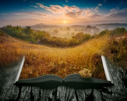 Summer misty valley in a light of sunrise on the pages of an open magical book. Majestic landscape. Nature concept.