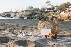 Summer mock-up. Vacation picnic still life. French straw basket with peaches fruit and croissant on beach sand. Blurred background with sea, white houses and boat. Mediterranean Mallorca island travel