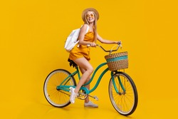 Summer Mode. Full-length Portrait Of Stylish Young Girl Riding Vintage Bicycle And Smiling Over Yellow Studio Background, Free Space