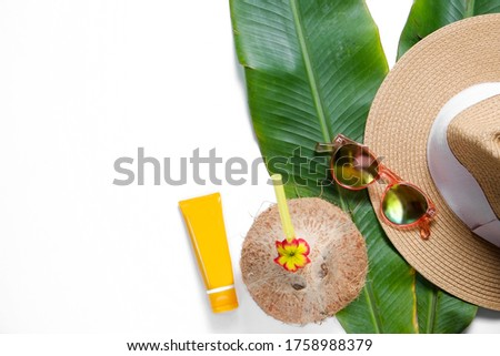 Summer mood concept. Tropical background w/ fresh whole coconut, mirrored lense sunglasses, broad brim straw hat and sunscreen on banana palm leaves. Flat lay, top view, close up copy space, isolated. Zdjęcia stock ©
