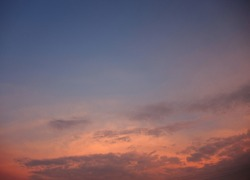 Summer morning photo of the sky at sunrise or sunset. Orange, pink and blue clouds in the sky lit by the rising sun.