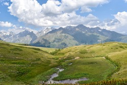 Summer mountain landscape in Svaneti region, Georgia, Asia. Snowcapped mountains in the background. Blue sky with clouds above. Georgian travel destination