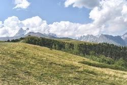 Summer mountain landscape near Mestia, Svaneti region, Georgia, Asia. Snowcapped mountains in the background. Blue sky with clouds above. Georgian travel destination.