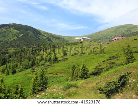 Summer mountain view with flowers and some snow on mountainside (with weather and biological stations buildings on Chornogora Ridge, Carpathian, Ukraine)