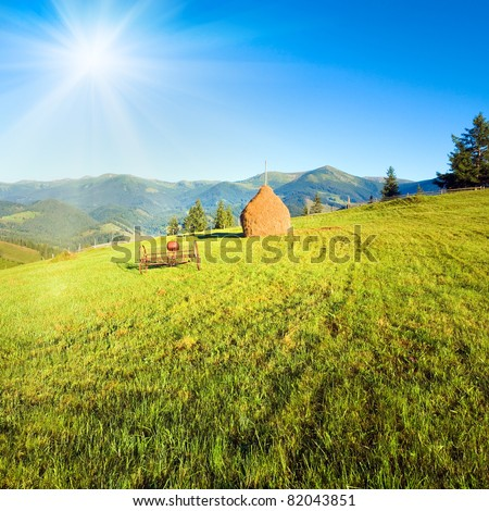 Summer mountain village outscirts with field, haystack and old mowing machine