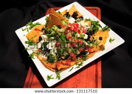 Summer Nachos with cheese and chicken served on a white plate