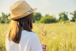 Summer nature, back view of child girl in straw hat tearing meadow grasses, copi space beautiful sunset meadow landscape