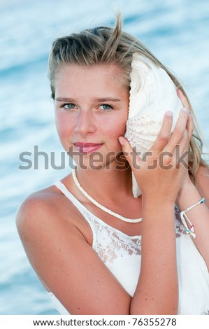 Summer on the beach - beautiful girl with shell in beach resort