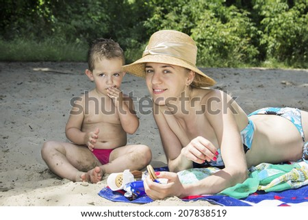 Summer on the beach near the bushes mom with a child eat cookies smiling woman.