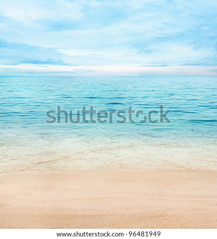 Summer or spring abstract background. Golden sand with blue ocean and cloudscape and sunset in the back.