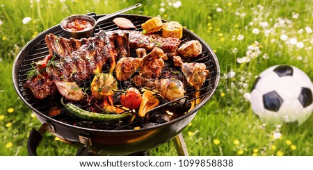 Summer or spring barbecue outdoors in a meadow with dandelions and a soccer ball with assorted vegetables, spicy spare ribs and chicken legs grilling on the fire #1099858838