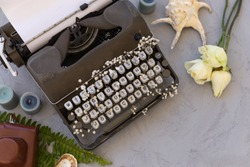 Summer or spring writing and freelance concept. Styped topview  photo of vintage typewriter with roses, leather vintage camera and seashell. Copy space. Horizontal composition.