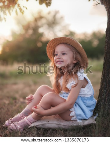 Summer outdoor portrait of beautiful happy child. Little girl wear a hat. Your kid sits at the park or forest outdoors, spring.