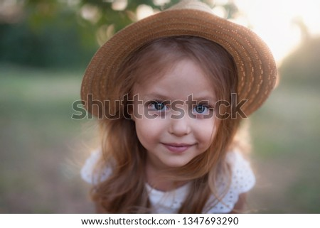 Summer outdoor portrait of beautiful happy child. Little girl wear a hat. Your kid walking in park or forest outdoors, spring.