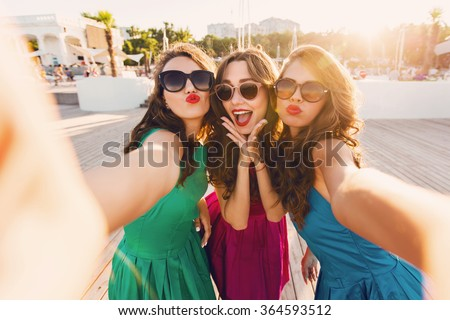 Summer outdoor portrait of three friends fun girls  taking photos with a smartphone at bright sunset. Group of happy women  taking self-portrait on their travel vacations. Wearing colorful dress.